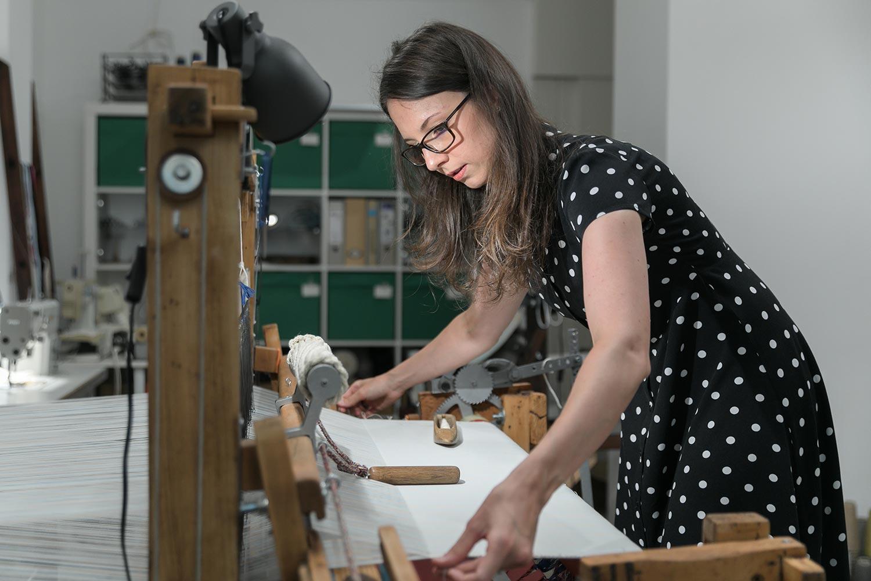 Krisztina Vandor is weaving at her studio in a polka dot dress