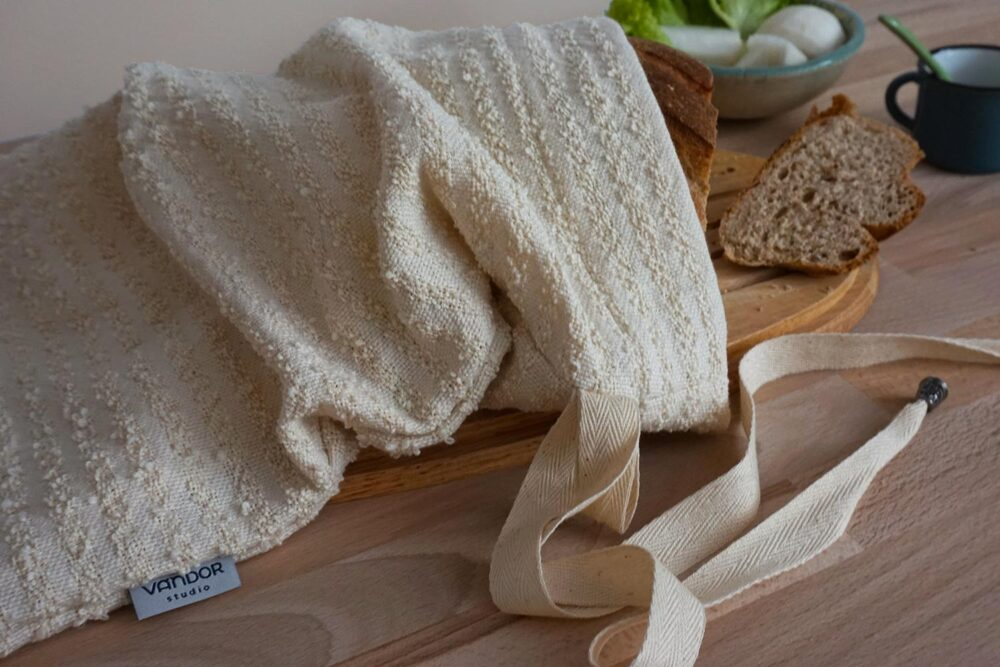cotton bread bag on a cutting board filled with a loaf