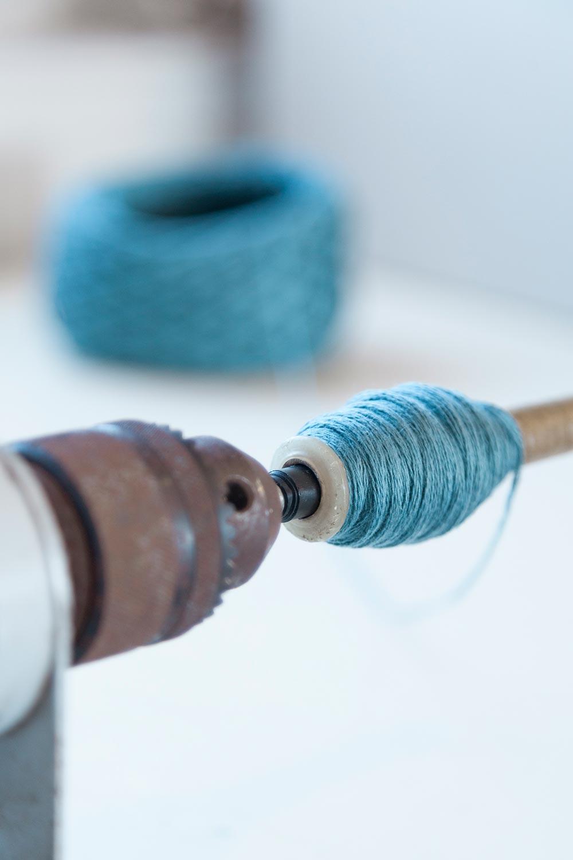 yarn winder with a weaving bobbin and turquoise yarn