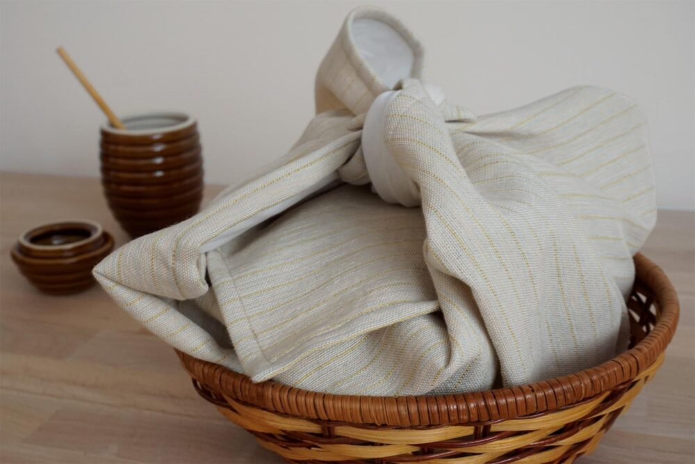 bread cloth in a basket covering a loaf