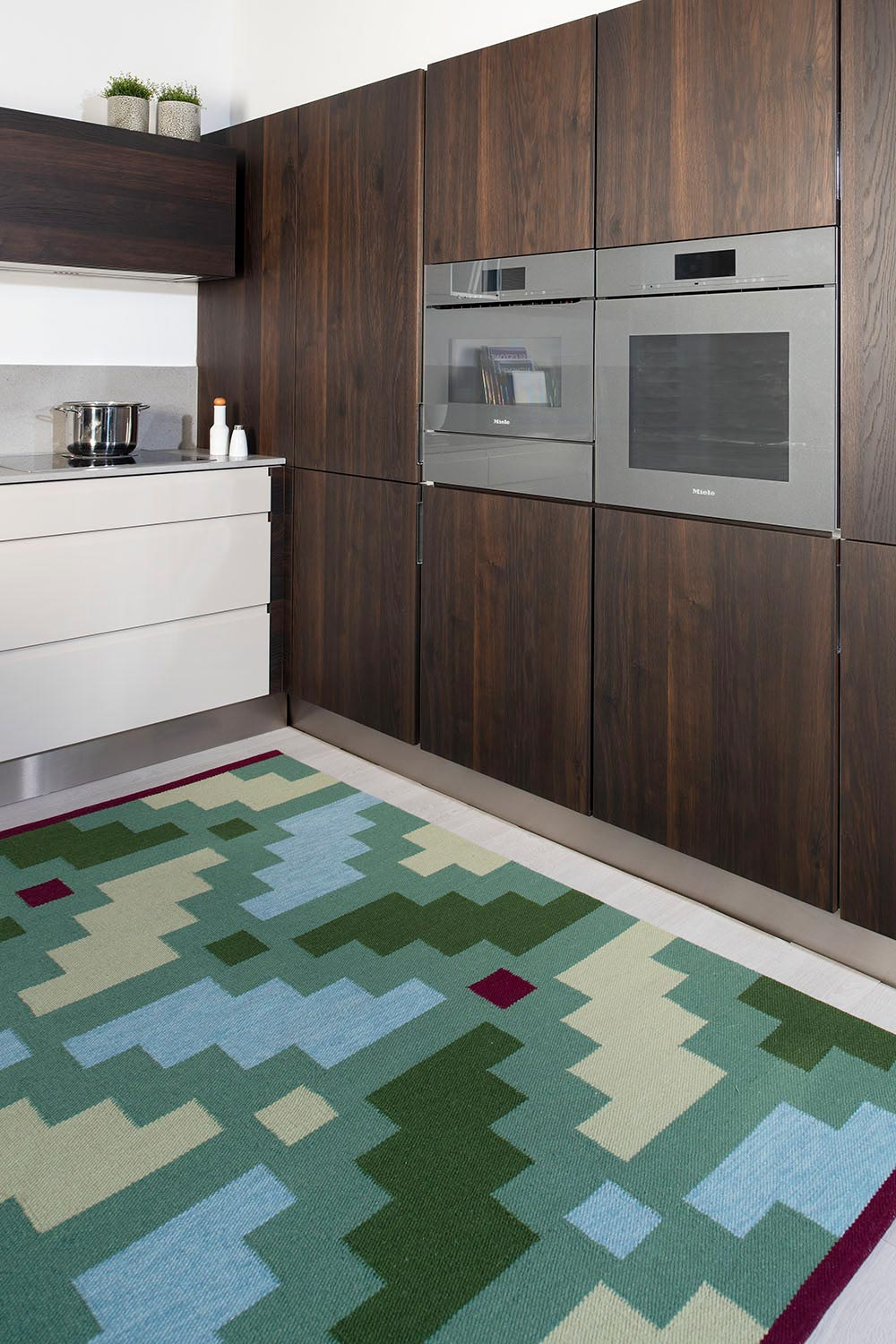 handwoven green patterned kilim type wool rug at a kitchen
