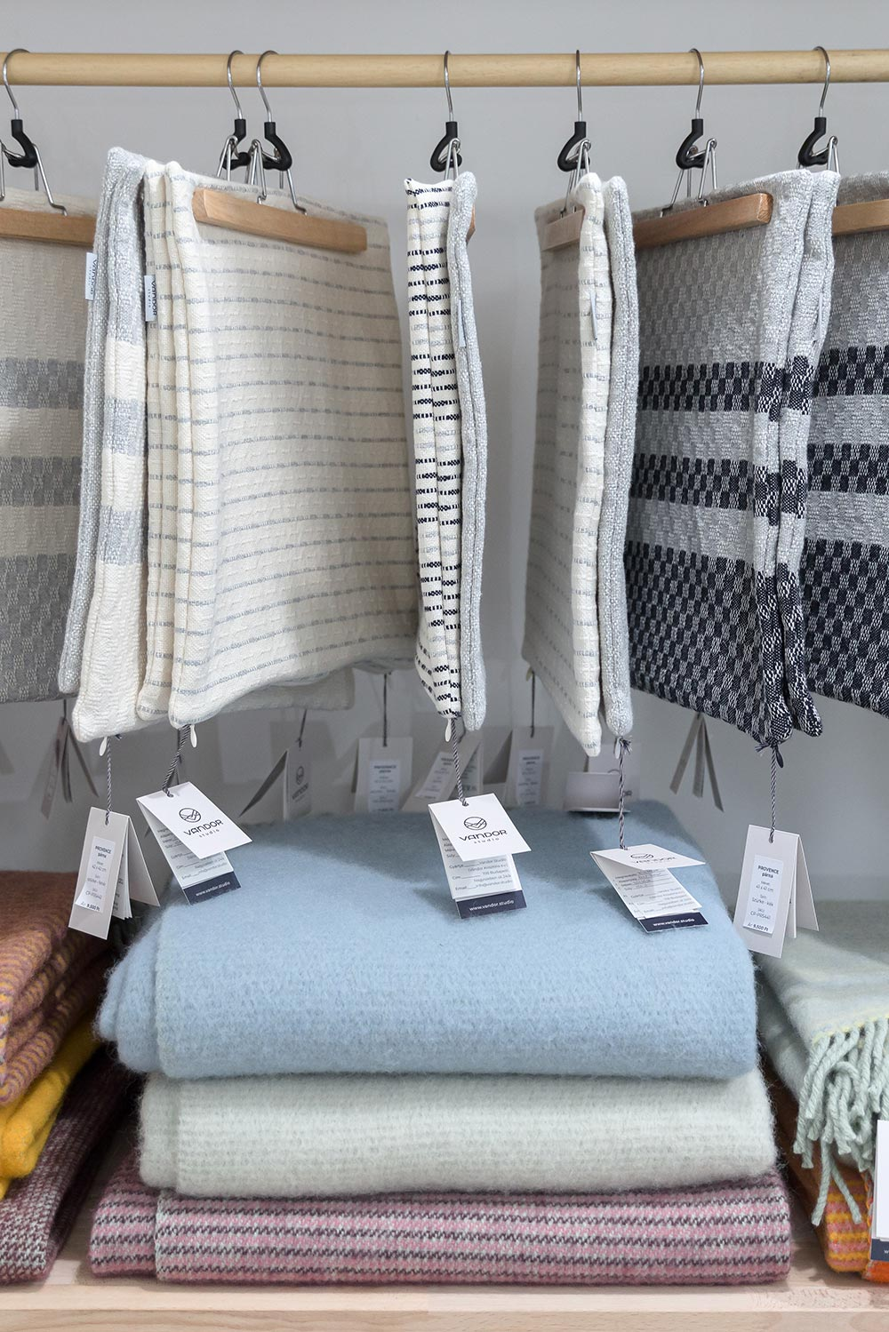 hanging cushions and folded blankets on a shelf at the studio