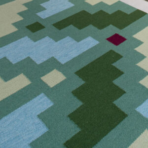 detail of a green rug with geometric pattern