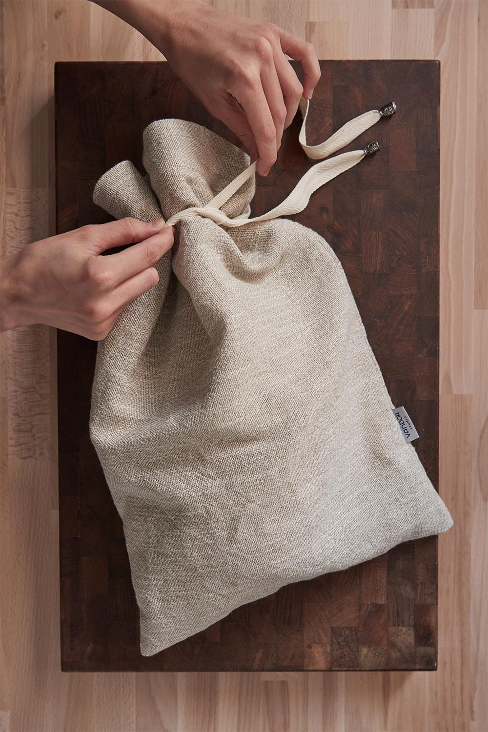 linen bread bag filled with bread on a cutting board
