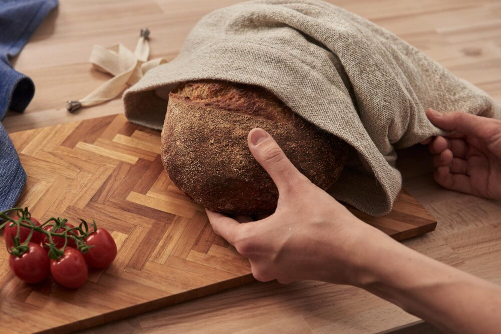 pulling out a loaf from a linen bread storage bag