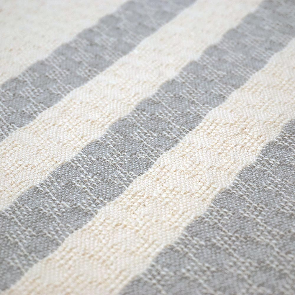 detail of a handwoven cushion with white and grey stripes