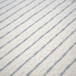 detail of a white and grey striped throw pillow