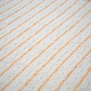 detail of a white and peach striped throw pillow