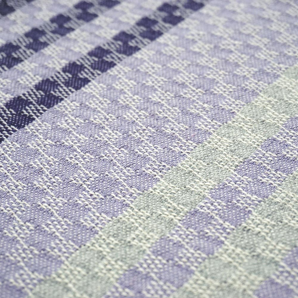 detail of a purple and grey striped cotton decorative pillow