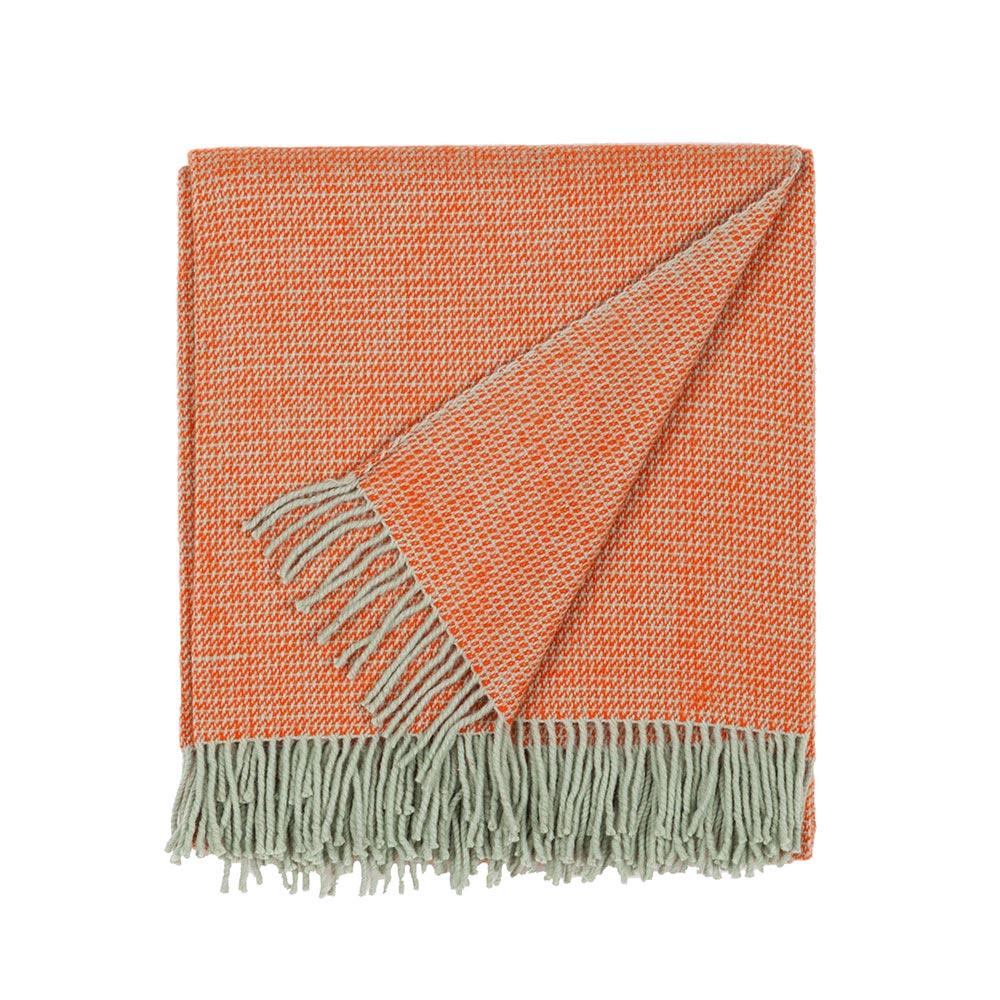 folded wool blanket in orange color with fringes