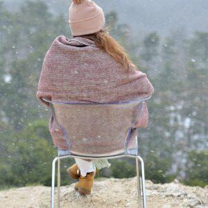 girl sitting in snowfall wrapped in purple wool blanket